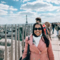 Aliya Bora on the top of the Arc De Triomphe with a view of the Eiffel Tower in the background in Paris, France