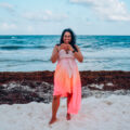 my favorite spots in Tulum - Aliya Bora holding up a heart sign on the beach in Tulum Mexico
